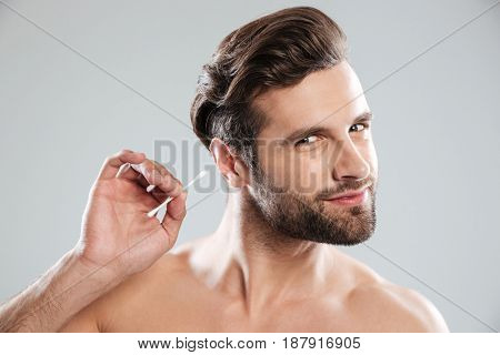 Young man with bristle using ear sticks isolated