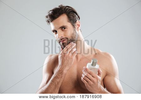 Young man touching his face while holding bottle perfume isolated