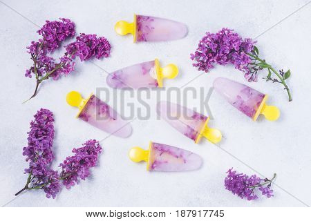 Popsicles with lilac flowers on gray stone background
