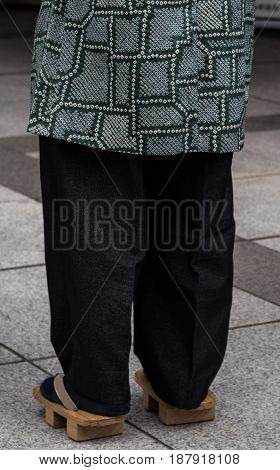 Asian man wearing traditional japanese wooden sandals Geta footwear and tabi socks on the streets of Tokyo, Japan