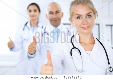 Happy doctor woman with medical staff at the hospital. Thumbs up