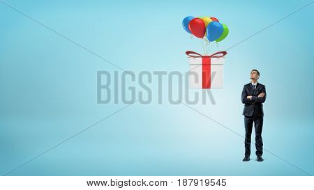 A small businessman looking up at a large gift box flying away on colorful balloons. Last minute deal. Bonuses and gifts.