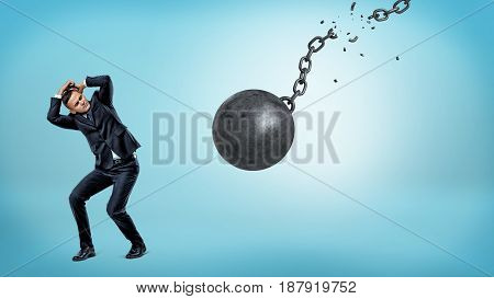 A small businessman trying to hide and cover himself from a falling wrecking ball with a torn chain. Inevitable problems. Business troubles. Dangerous job.