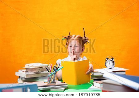 The Redhead teen girl with lot of books sitting at table on orange studio background. The education and back to school concept