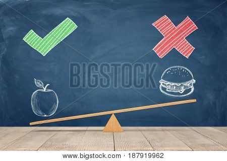 A wooden seesaw on blue chalkboard background where a painted apple overweighs a sandwich. Healthy eating. Staying in shape. Choose your diet.