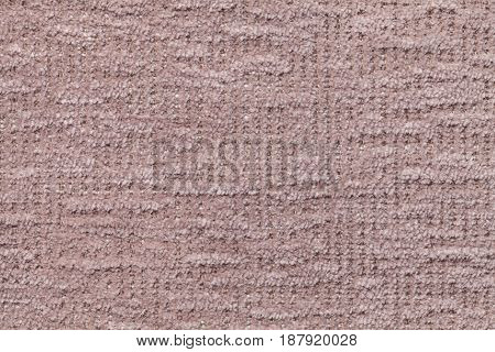 Light brown fluffy background of soft fleecy cloth. Texture of taupe plush furry textile closeup.