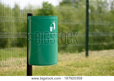 A green metal trash bin in the park or outside of a public utility building