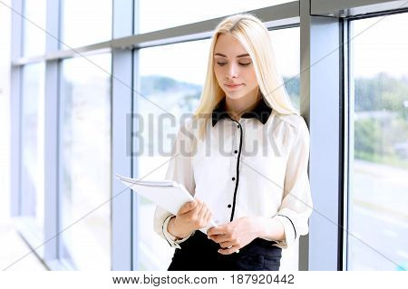 Happy modern business woman with financial report is in office hall.