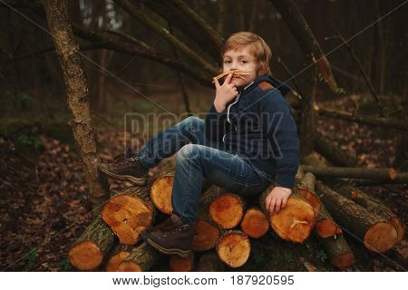 photo of little sweet lumberjack in autumn forest