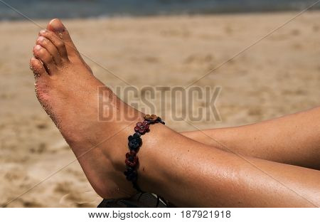 A foot of a young lady relaxing on the beach