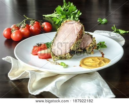 Grilled meat on white plate with tomatoes chives and dark hot sauce