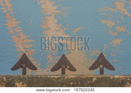 Abstract image arrow head shape of steel fence and blue grunge wall background.