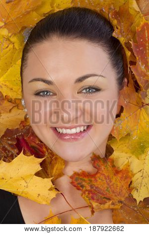 Close up of woman face in yellow autumn leaves