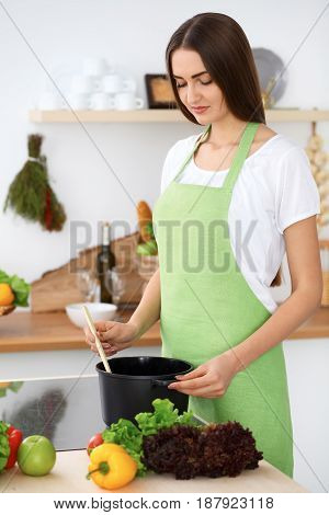 Beautiful Hispanic woman in a green apron cooking in the kitchen. Housewife found a new recipe for her soup