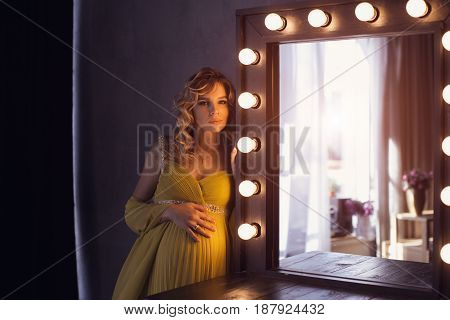 Pregnant woman. Romantic portait photo of beautiful blonde girl posing in sexy evening dress looking at camera at home. Indoor shot against gray wall and mirror.