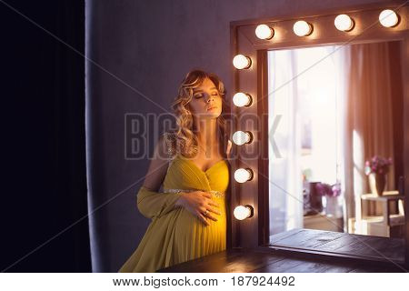 Pregnant woman. Romantic portait photo of beautiful blonde girl posing in sexy evening dress with closed eyes dreaming at home. Indoor shot against gray wall and mirror.