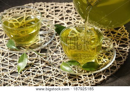 Pouring green tea into glass cup from teapot, closeup