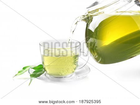 Pouring glass tea into glass cup from teapot on white background