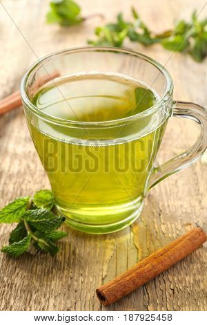 Cup of tea with mint leaves and cinnamon on wooden table