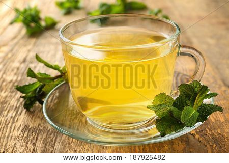 Cup of tea with mint leaves on wooden table