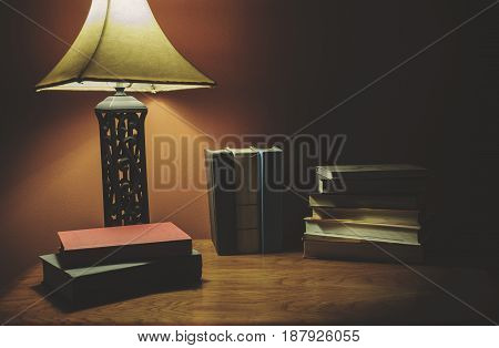Stack Of Hardcover Book On A Wood Table With Lamp