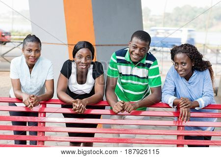 group of young friends in a park leaning on a bench with a beautiful smile.