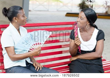 two young women sitting  on a bench are talking and listen carefully.