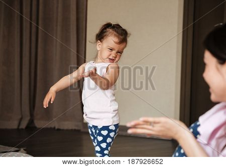 Image of pretty young mother talking with her little daughter indoors. Looking aside.