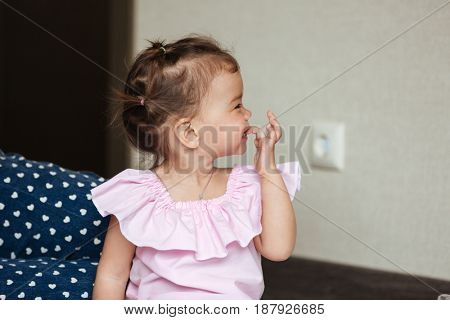 Photo of happy young little girl sitting near mom indoors. Looking aside.