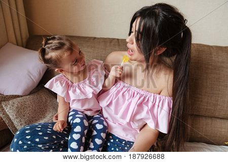 Image of young pretty mother sitting on sofa with her little daughter indoors. Looking aside.