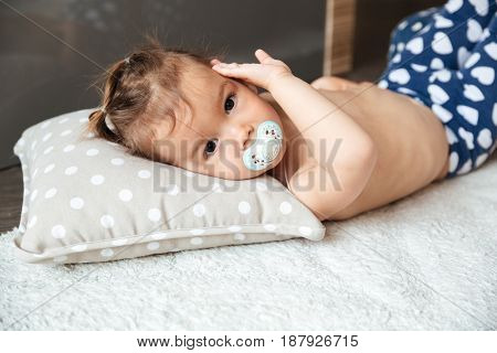Image of cute little girl child indoors with nipple lies on bed. Looking at camera.