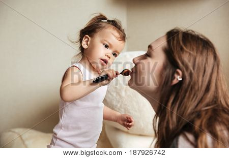 Picture of little cute girl does a makeup for her happy young mother sitting on bed indoors. Looking aside.