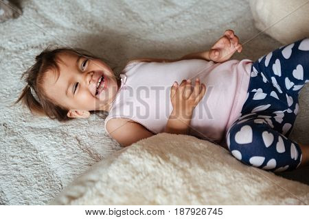 Picture of little cute child girl lies on bed indoors. Looking aside.