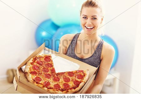 Happy woman with pizza in gym