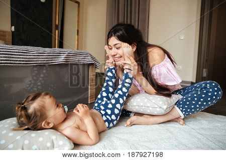 Picture of happy young mother have fun with her little girl child indoors. Looking aside.