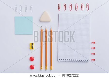 Top view picture of a lot of office supplies on the white background table