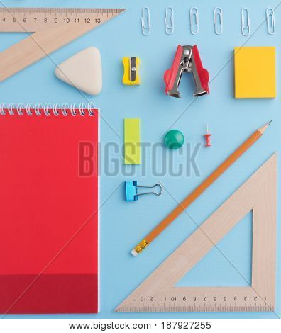 Top view picture of office supplies on the blue background table