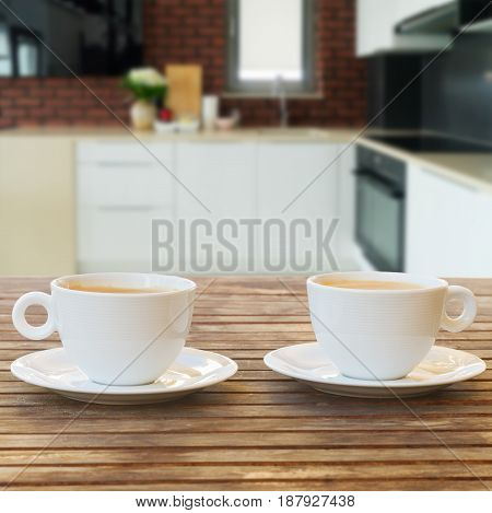Empty kitchen table top with two coffee cups, modern kitchen in background