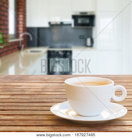 Empty kitchen table top with coffee cups, modern kitchen in background