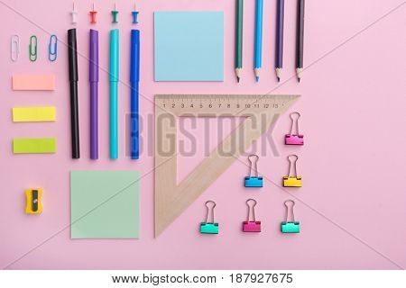 Top view image of a lot of office supplies on the pink background table
