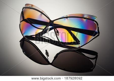 Stylish polarized colorful reflected sunglasses in metal frame with folded ear arms unfocused background and removed logos