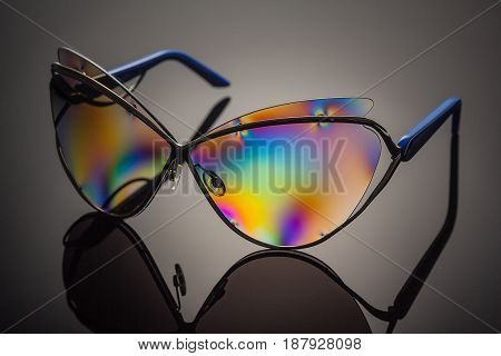 Stylish polarized colorful reflected sunglasses in metal frame with unfocused background and removed logos