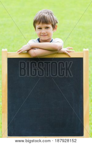 Happy kid standing at the blackboard. Green background. Copy space for text.