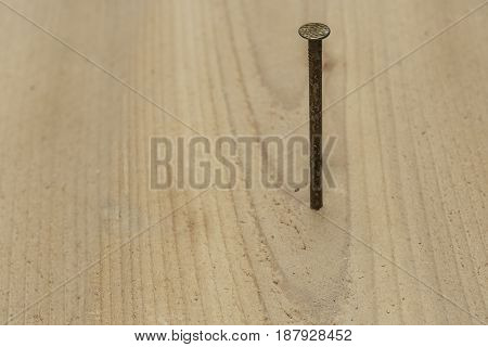 single nail being driven into a board