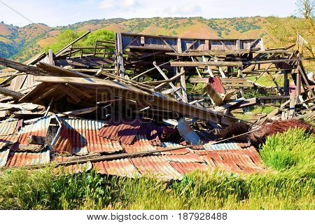 Dilapidated collapsed wooden barn taken in a field