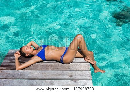 Luxury travel woman tanning on overwater resort deck over turquoise ocean water in Tahiti, French Polynesia island. Vacation destination.