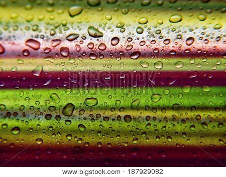 Drops of dew on a multi-colored metal background. Close-up. Positive background.