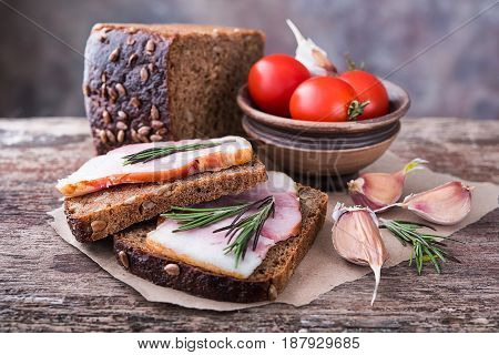 Traditional ukrainian sandwiches made of brown rye bread and smoked lard on a piece of brown paper and natural wooden textured surface with unfocused background. On this photo it is accompanied by tomatoes garlic and rosemary.