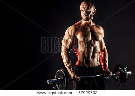 Studio portrait of topless bodybuilder performing biceps exercise with concentrated face over black background with smoke and light. Cutout. poster
