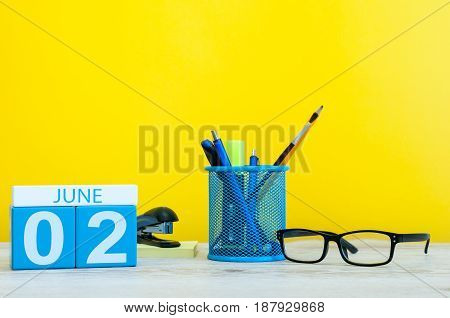 June 2nd. Day 2 of month, calendar on yellow background with office suplies. Summer day, empty space for text.